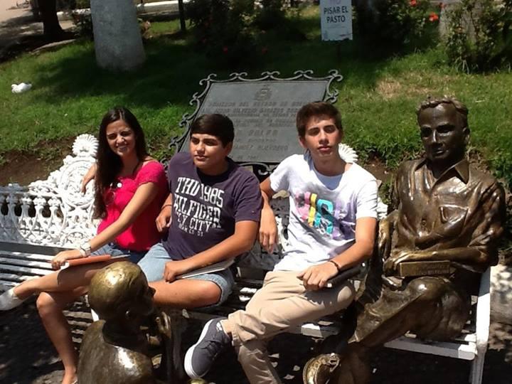 Visitando Comala, tierra de Juan Rulfo e hijos posando junto a la estatua en la plaza principal, cada uno con su libro viajero.