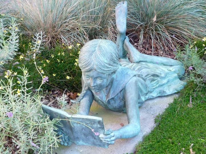 Niña leyendo cuentos de hadas en el jardín literario.